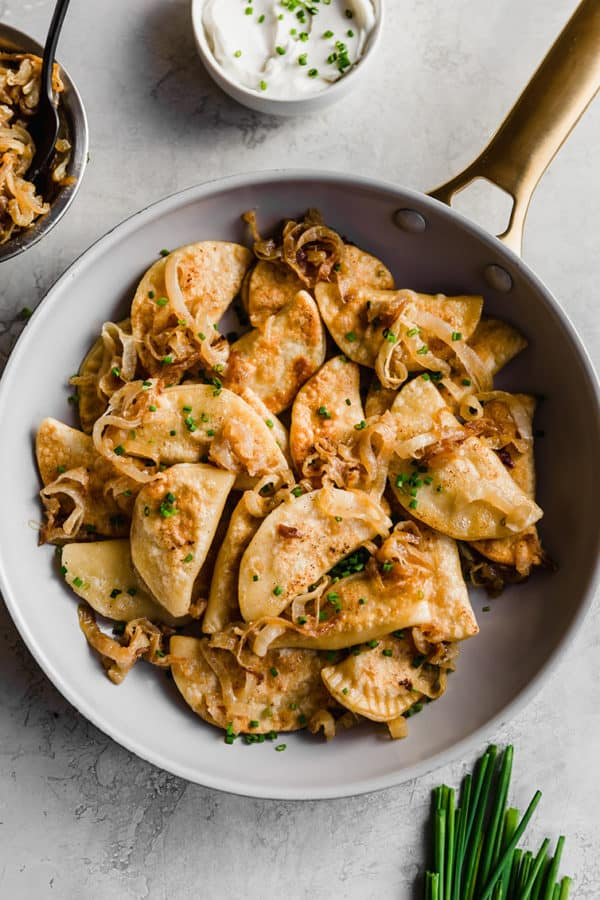 A frying pan full of pierogi with caramelized onion.