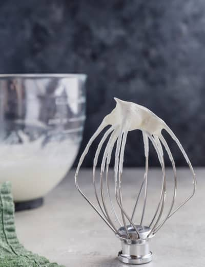 A whisk attachment standing upright with whipped cream on top, with a bowl of whipped cream behind.