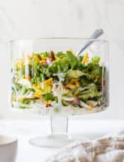 A glass trifle bowl with seven layer salad.
