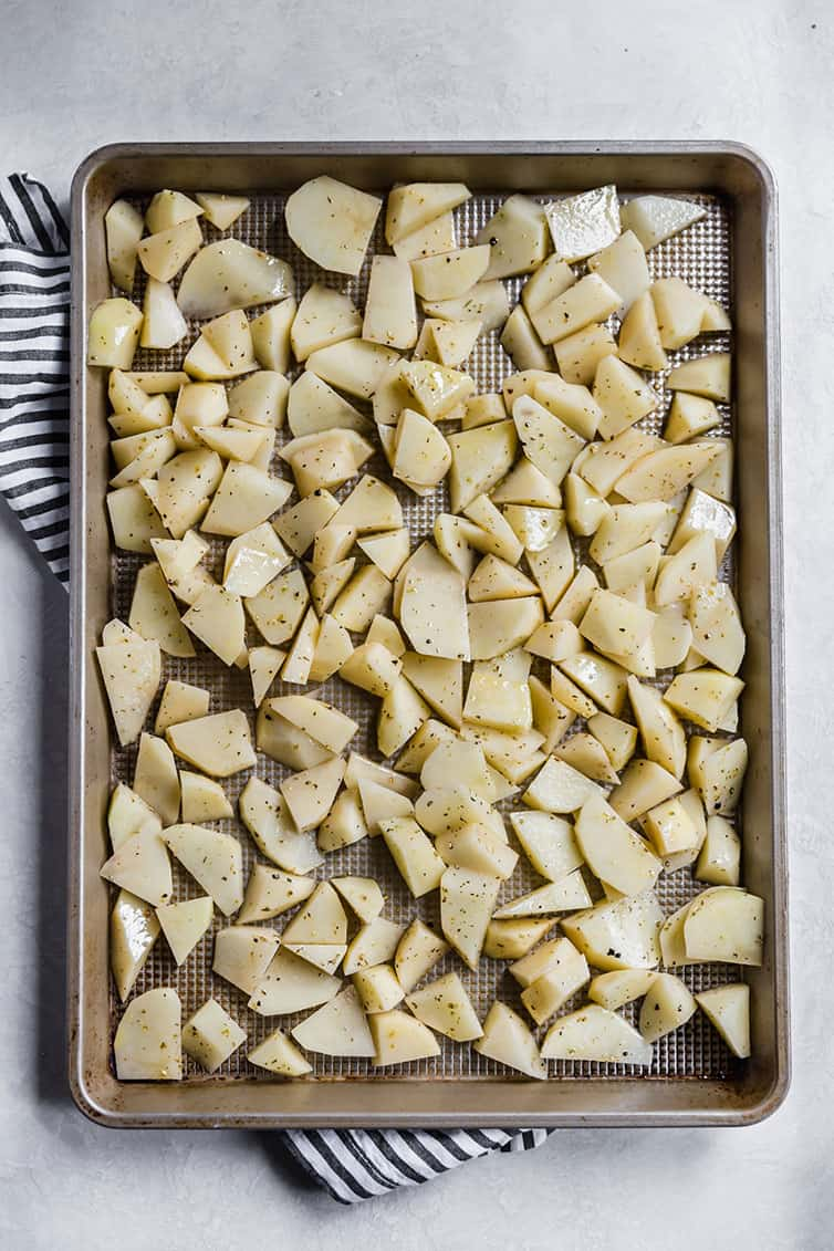 Pan of sliced potatoes tossed with olive oil and Italian seasoning.