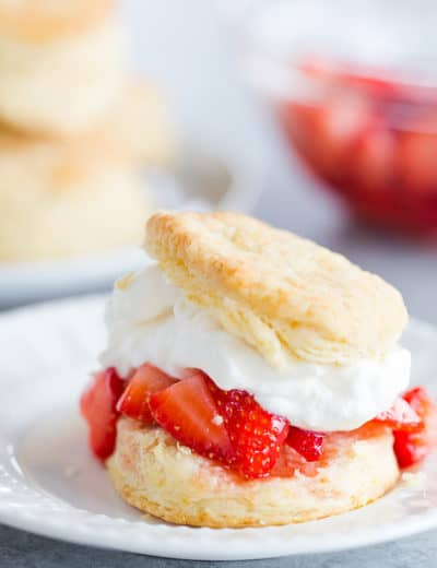 Assembled strawberry shortcake - split buttermilk biscuit with macerated strawberries and fresh whipped cream.