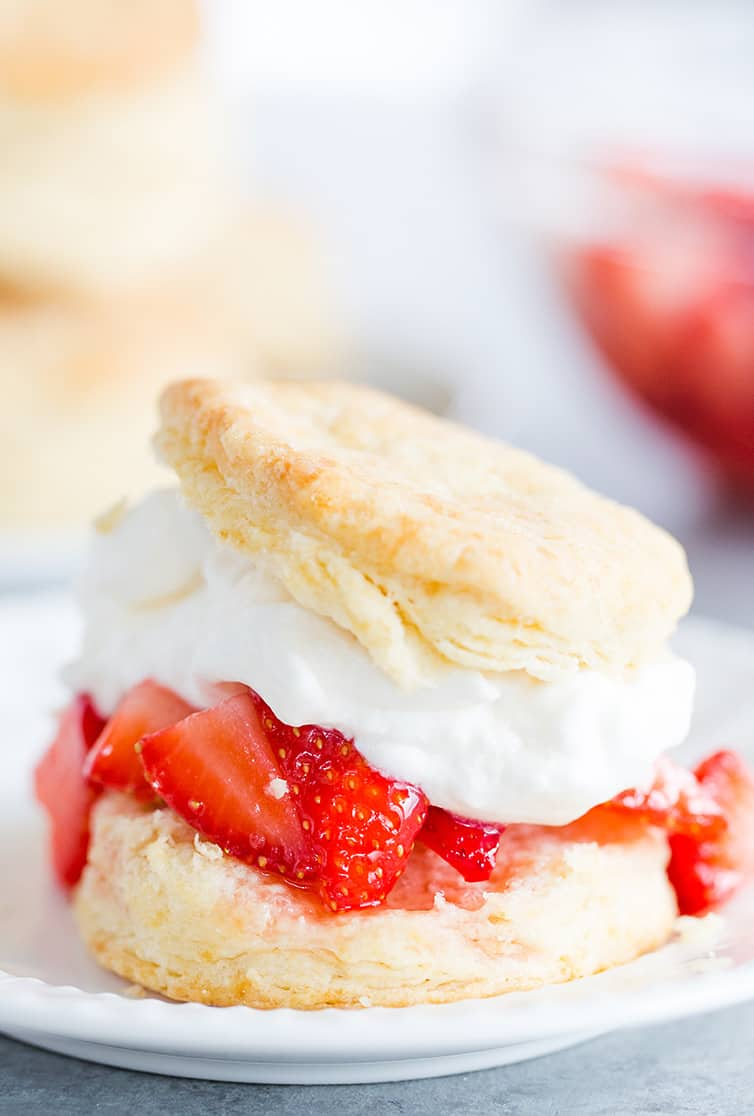 An assembled strawberry shortcake with biscuit, strawberries and whipped cream.