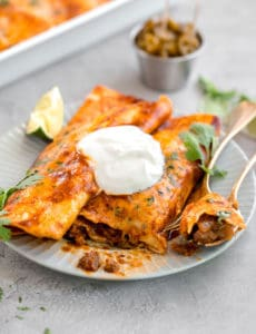 Two beef enchiladas on a plate, with a fork cut into one.