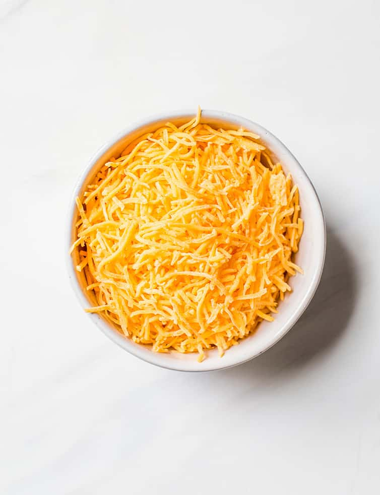 A prep bowl with shredded cheddar cheese.