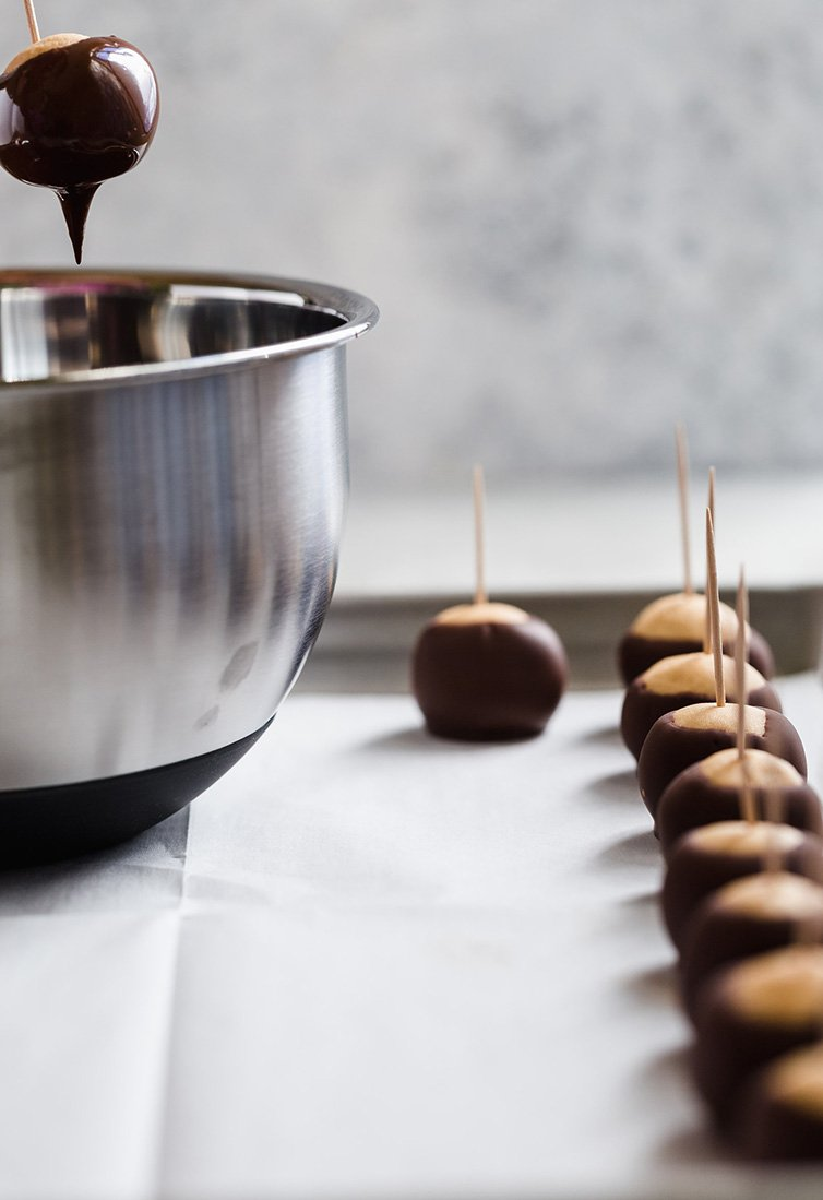 Dipping a buckeye into chocolate with finished ones on a pan.
