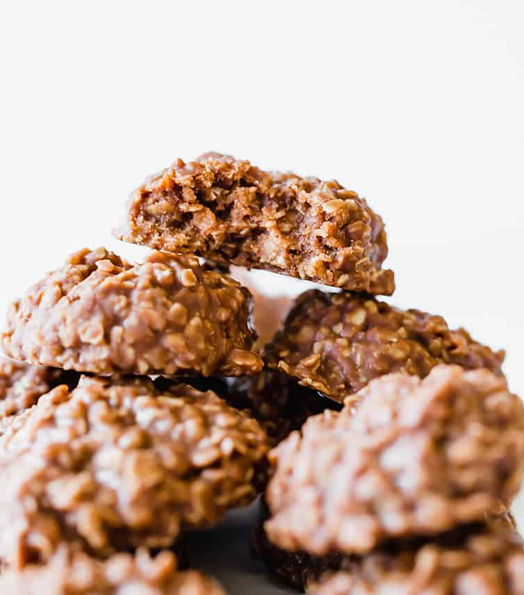 A pile of no bake cookies with a half-eaten one on top.
