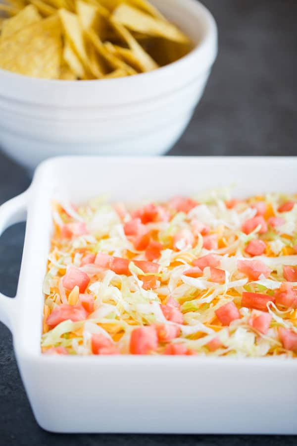 Taco dip in a white casserole dish with a bowl of chips in the background.