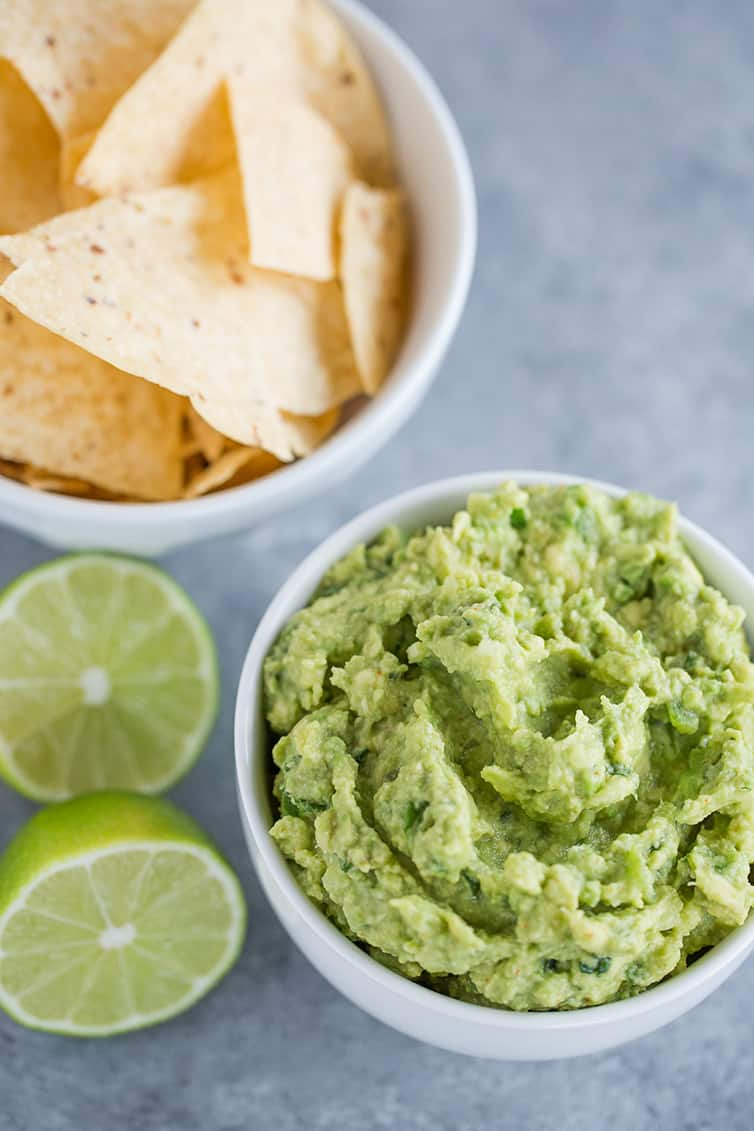 A bowl of guacamole, tortilla chips, and a lime sliced in half.