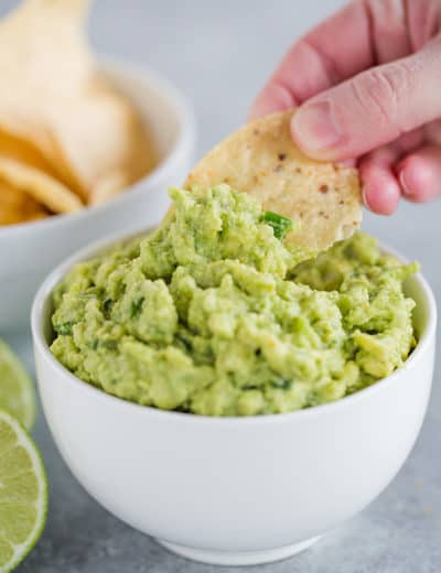 Someone dipping a tortilla chip into a bowl of guacamole.