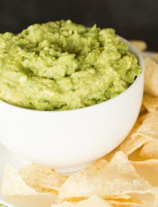 A bowl of guacamole set on a plate with tortilla chips.