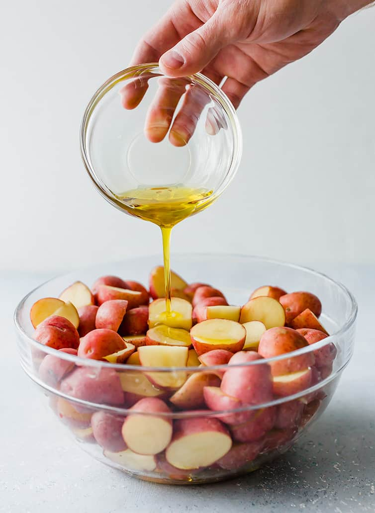 Drizzling olive oil over a bowl of red potatoes.
