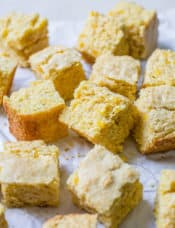 Squares of cornbread on a piece of parchment paper.