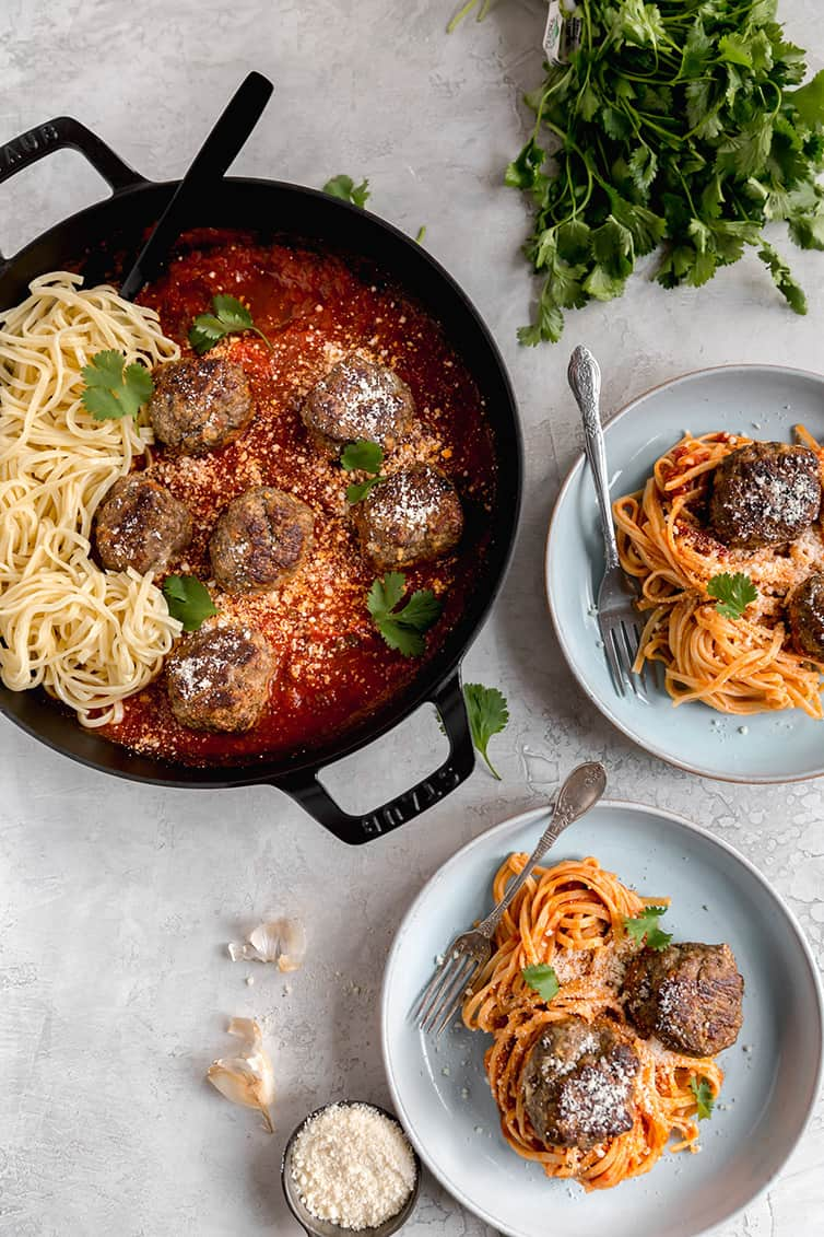 A pot of sauce with meatballs and spaghetti, with two plated servings next to it.