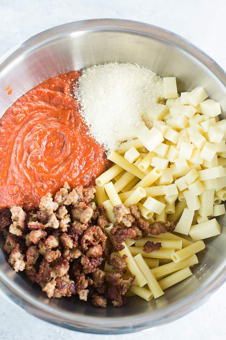 A big bowl with all of the ingredients for baked ziti.
