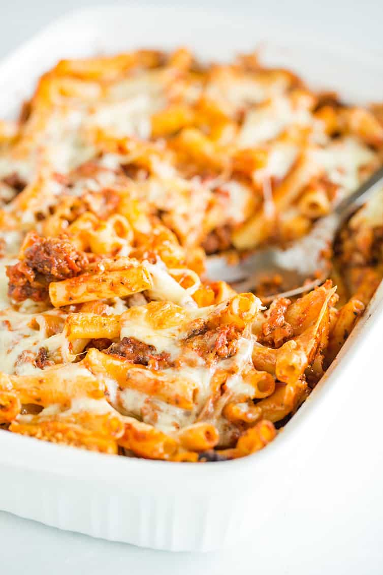 Spooning out a scoop of baked ziti from the pan.