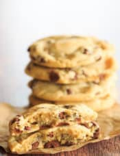 One chocolate chip cookie split in half in front of a stack of cookies.