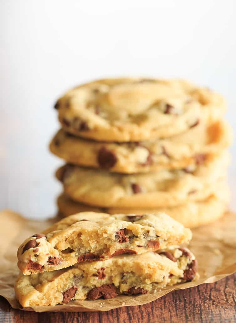 One Chocolate Chip Cookie Split In Half Front Of A Stack Cookies