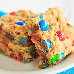 Monster Cookie Bars - Peanut butter dough is loaded with oats, chocolate chips and M&M's. | https://www.browneyedbaker.com/monster-cookie-bars/