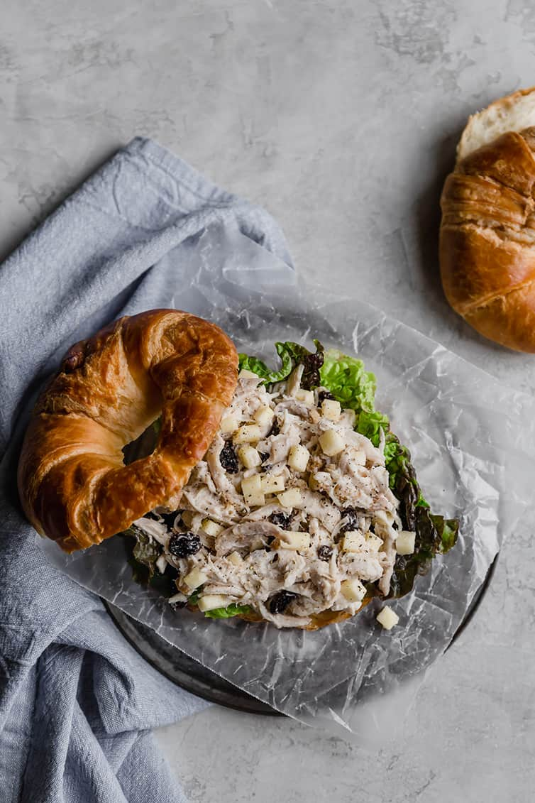 A chicken salad sandwich on croissant with the top off.