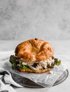 Chicken salad sandwich on a croissant placed on wax paper on a silver plate.