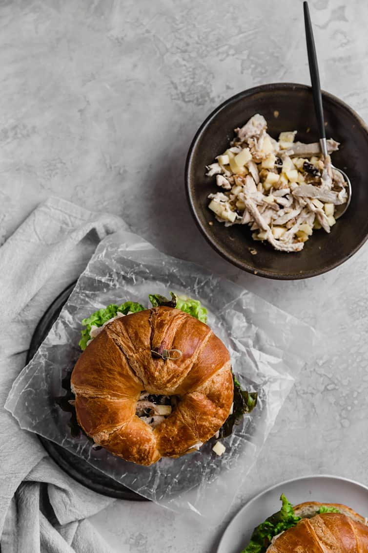 An overhead photo of a chicken salad sandwich on croissant with a bowl of chicken salad filling next to it.