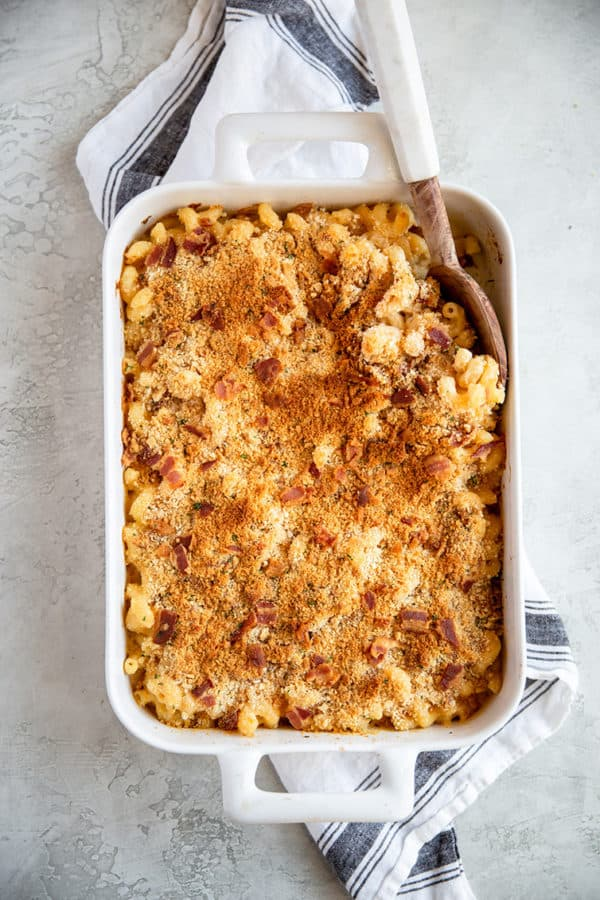 A white casserole dish with baked mac and cheese