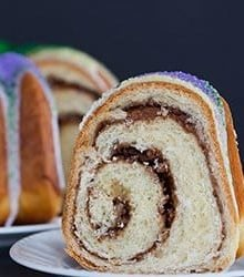 A festive King Cake for Mardi Gras - filled with a pecan, brown sugar and cinnamon swirl - baked into a Bundt pan and decorated with colored sanding sugars.