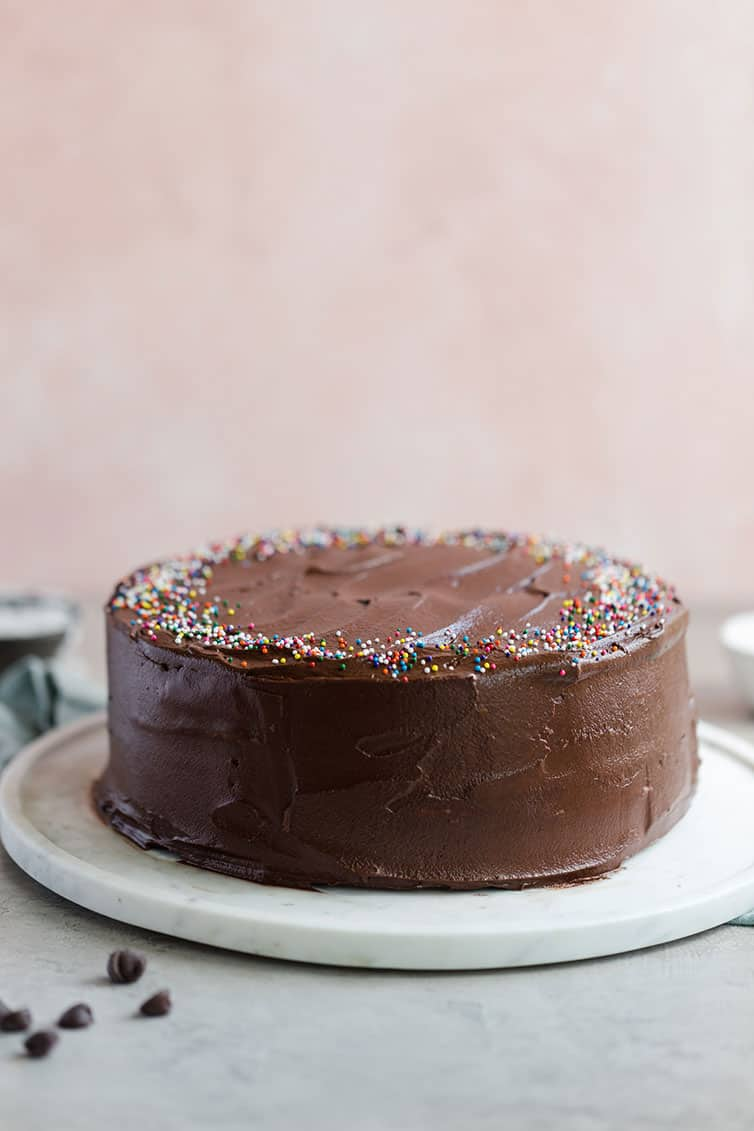 Cake covered in chocolate frosting on a platter.