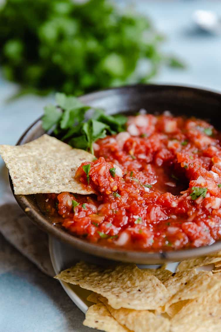 A bowl of salsa with a chip dipped into it.