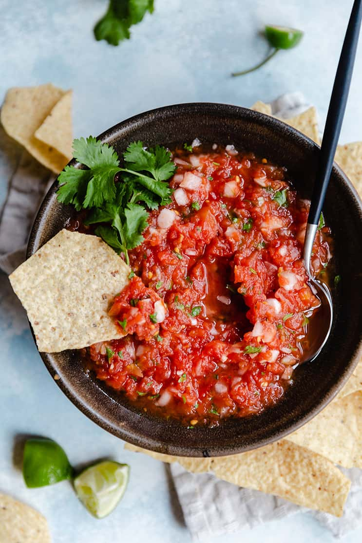 A bowl of salsa with a spoon on one side and a tortilla chip dipped in.