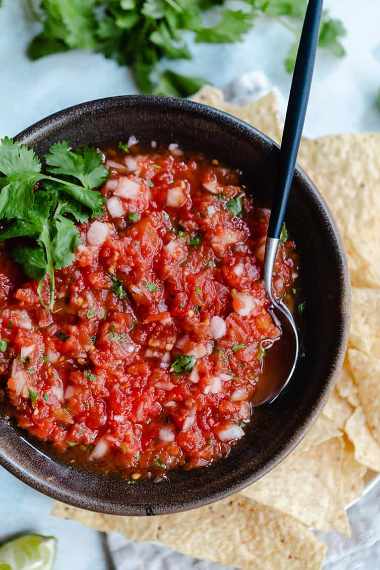 A bowl of salsa with a spoon in it and tortilla chips on the side.