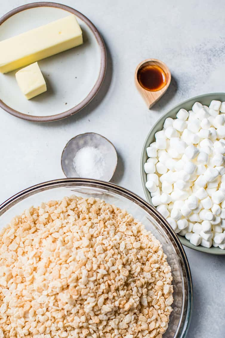 Ingredients for rice krispie treats in bowls - rice krispies cereal, marshmallows, salt, vanilla, and butter.