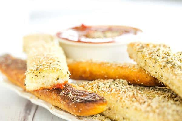 A copycat recipe for Pizza Hut breadsticks, made from scratch. Chewy, buttery, loaded with seasonings and an easy dipping sauce!