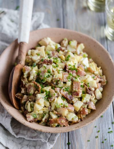 A bowl of potato salad with a serving spoon.