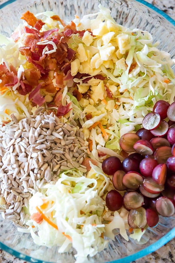 A loaded cole slaw recipe loaded with cheese, bacon, grapes, and sunflower seeds. A great addition to your summer picnic!