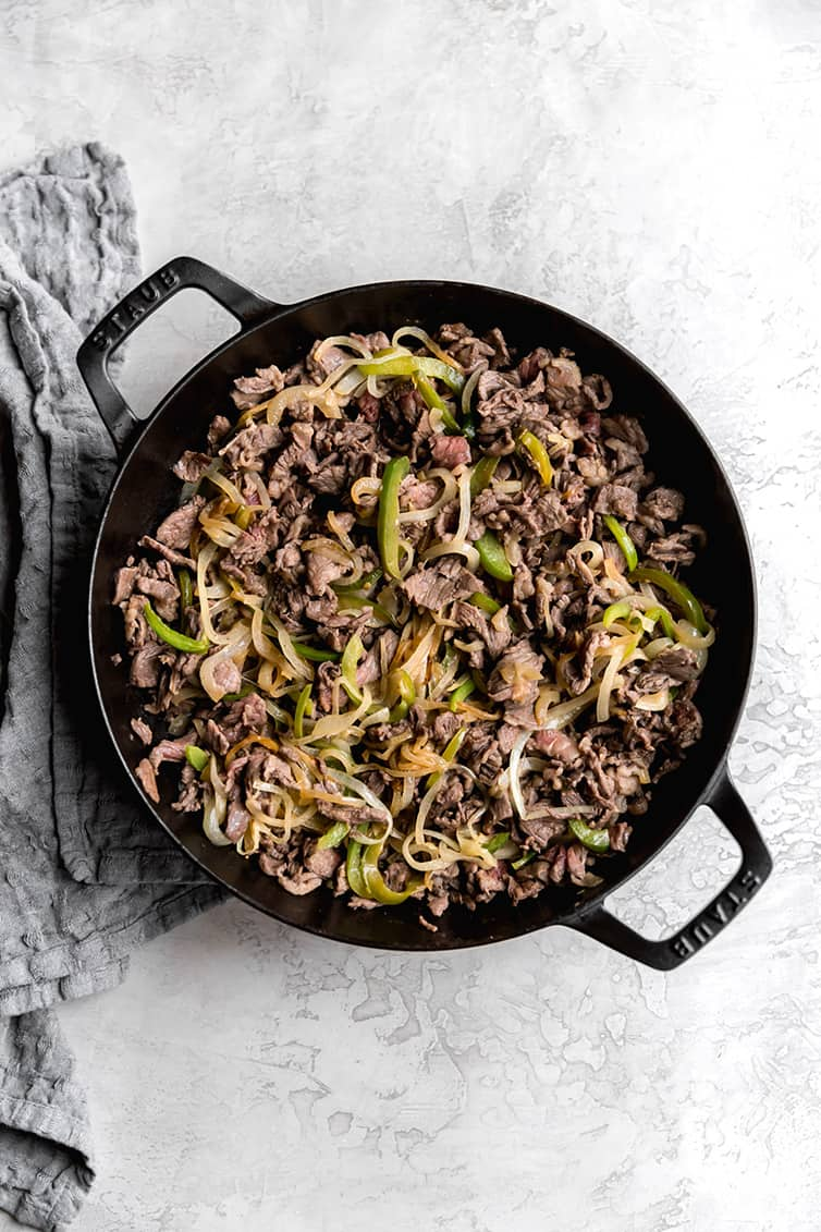 A saute pan with steak, onions and green peppers.