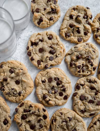 Chocolate chip cookies on wax paper with glasses of milk.