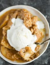 A plate of apple crisp with a scoop of ice cream on top.