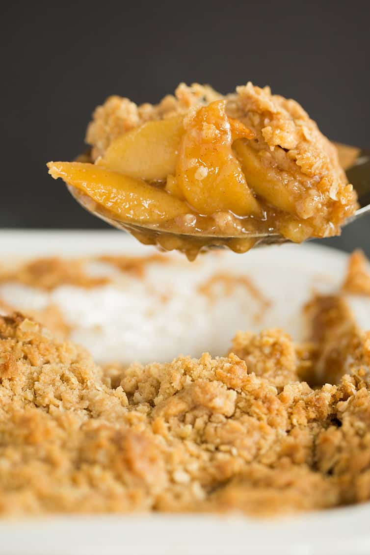 A spoonful of apple crisp being scooped out of the pan.