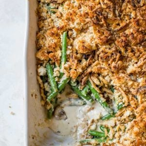 A pan of green bean casserole with a corner scooped out.