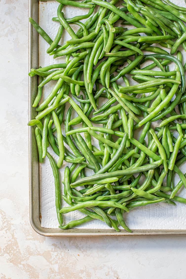 Fresh green beans boiled and draining on paper towels.