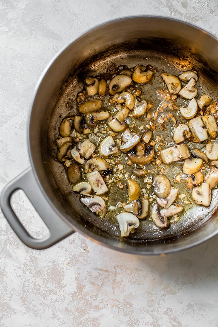 Sauteed mushrooms and onions in a large pot.