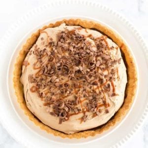 Milky Way Tart - A pate sucree crust is filled with caramel sauce and whipped milk chocolate ganache, then topped with a drizzle of caramel and chocolate curls.