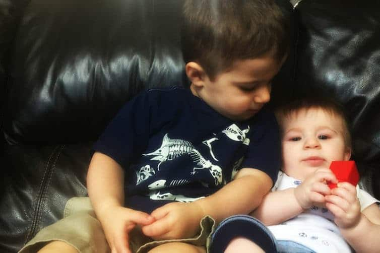 Joseph and Dominic snuggling on the couch.