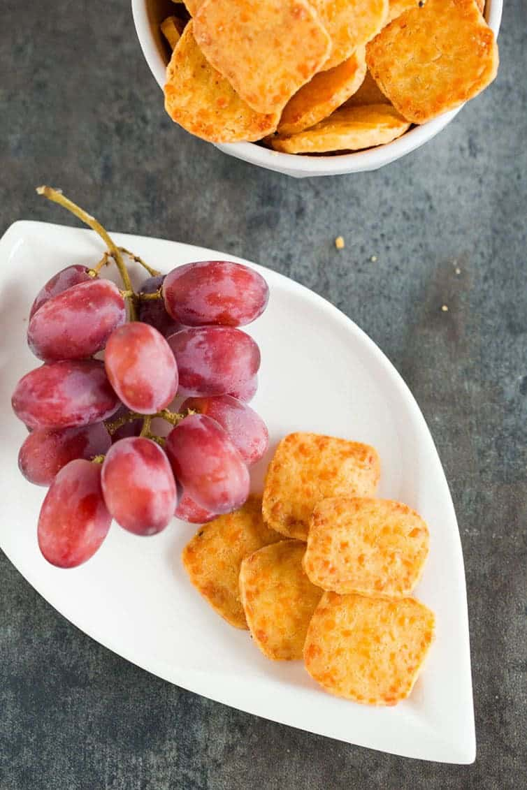 A plate of homemade cheese crackers with red grapes.