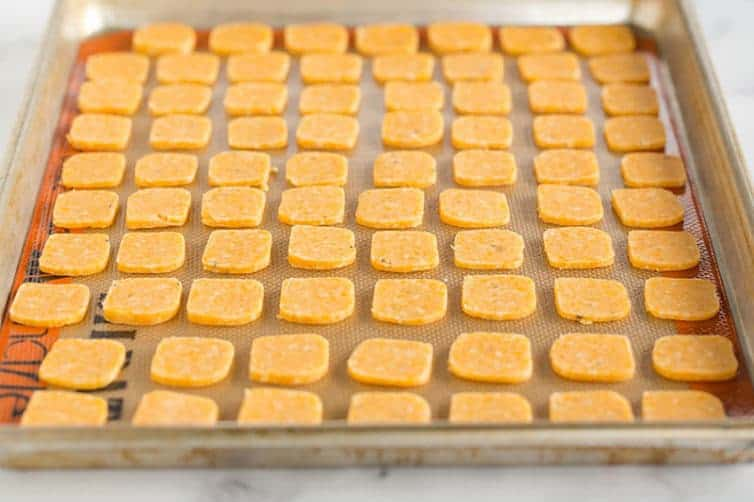 Spicy cheese crackers on a sheet pan, waiting to be baked.