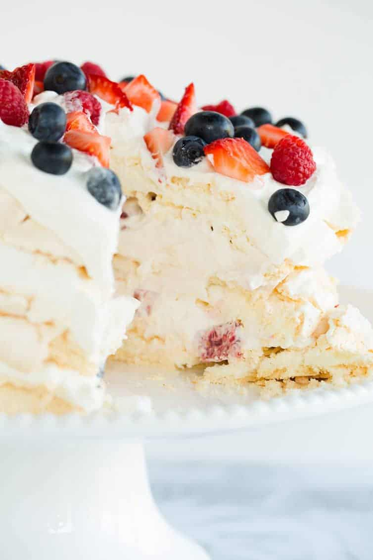 Pavlova layer cake sliced into with whipped cream and berries.