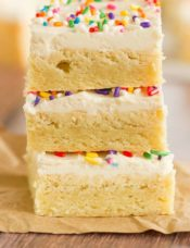 A stack of three sugar cookie bars with frosting and sprinkles.