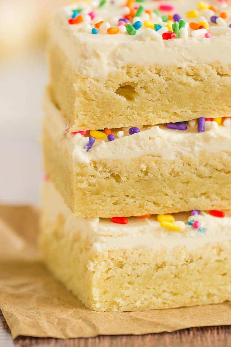 A close-up shot of a stack of frosted sugar cookie bars.