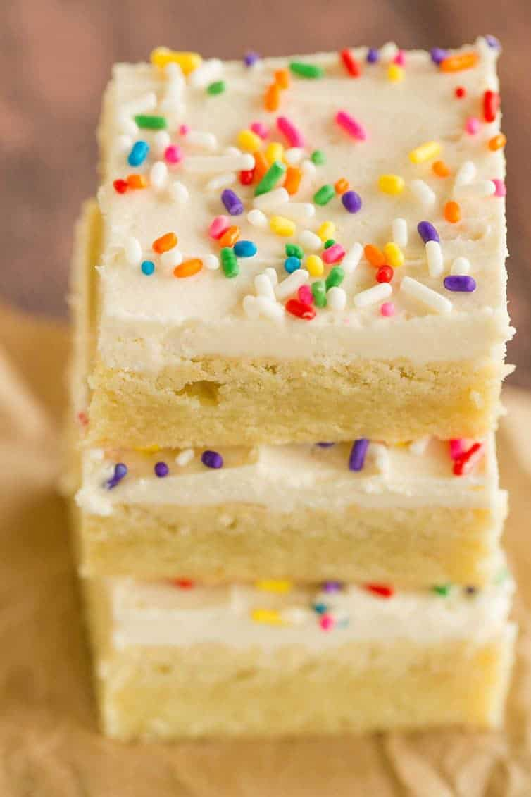 An overhead shot of a stack of frosted sugar cookie bars.